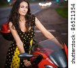 Portrait of pretty dark-haired young woman wearing dress, standing near red motorbike at road. - stock photo