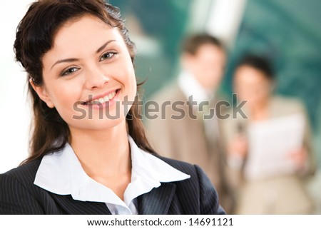 Portrait of pretty employee looking at camera with smile in working environment