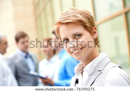 Portrait of pretty employee smiling at camera in natural environment - stock photo