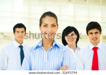 Portrait of pretty employee smiling at camera with business partners at background