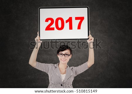 Portrait of pretty entrepreneur holding a white billboard with the number 2017