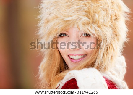 Portrait of pretty fashionable woman in fall forest park. Gorgeous young girl in fur winter hat. Autumn fashion.