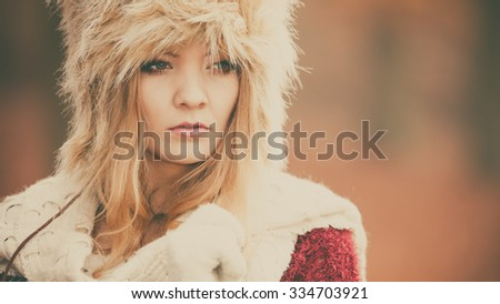 Portrait of pretty fashionable woman in fall forest park. Gorgeous young girl in fur winter hat and sweater pullover. Autumn fashion. Instagram filter.