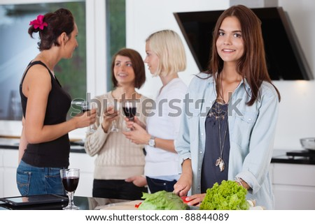 Portrait of pretty female cutting vegetables while her friends having drink in background
