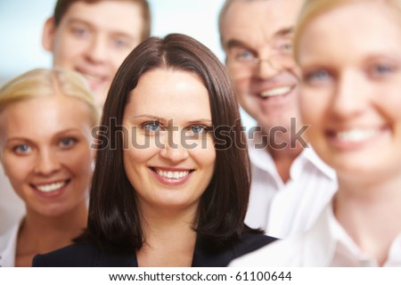 Portrait of pretty female looking at camera surrounded by her colleagues