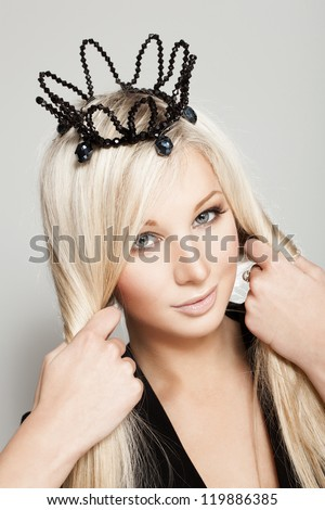 portrait of pretty female model with fresh daily makeup and long bright hair on grey background. Fashion shiny highlighter on skin, sexy glossy lips makeup and black crown - stock photo
