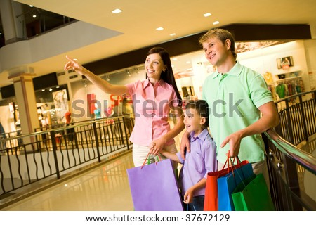 Portrait of pretty female showing something to her husband and son during shopping - stock photo