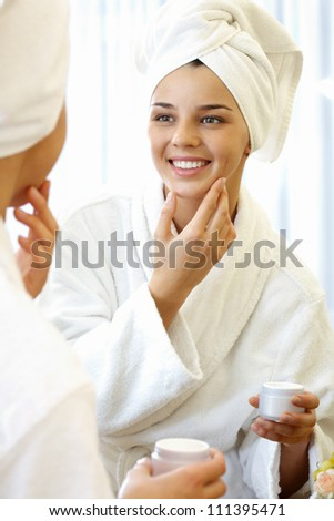 Portrait of pretty female with towel on head applying cream onto her face and smiling