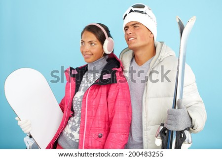Portrait of pretty girl and handsome man in winterwear holding snowboard and skis - stock photo