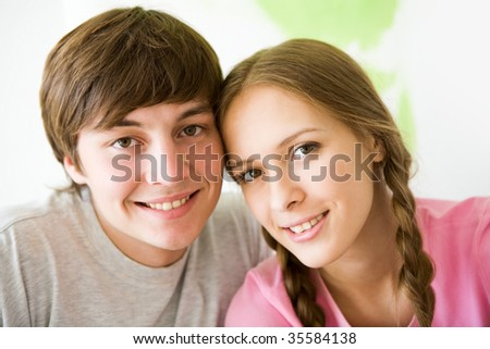 Portrait of pretty girl and her boyfriend looking at camera with smiles
