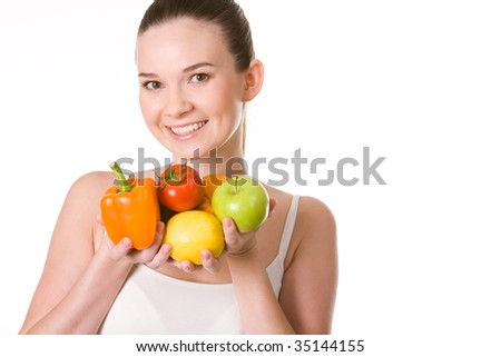 Portrait of pretty girl holding different fruits and vegetables in hands and smiling