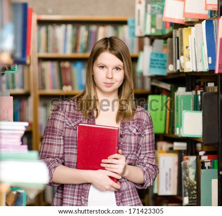 Portrait of pretty girl in library looking at camera - stock photo