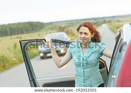 Portrait of Pretty girl is standing near the modern car against driving auto. Focus point on face Young adult traveling redhead woman based on door automobile on green grass field, forest background  - stock photo