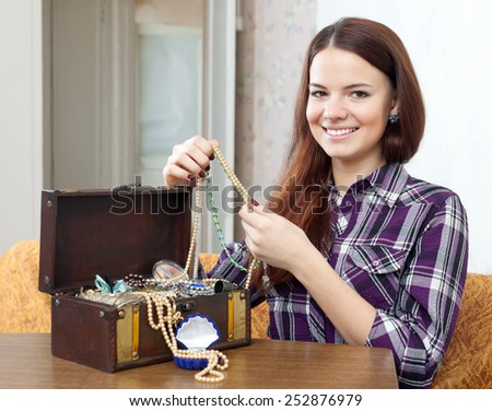 portrait of pretty girl looks jewelry in treasure chest at home - stock photo