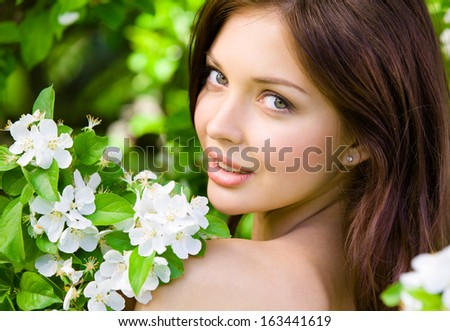 Portrait of pretty girl near the blossomed tree in the park. Concept of youth and natural beauty - stock photo