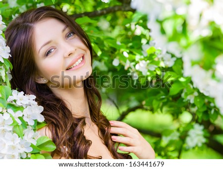 Portrait of pretty girl near the flowered tree in the park. Concept of youth and natural beauty - stock photo