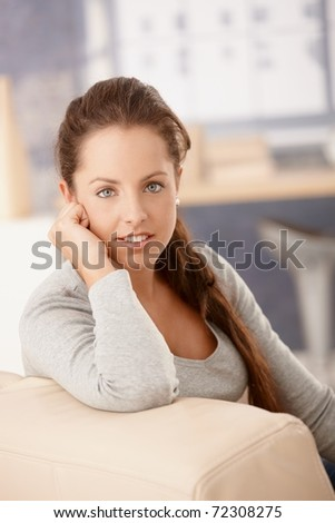 Portrait of pretty girl sitting on sofa at home, smiling.? - stock photo