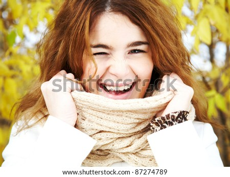 Portrait of pretty girl touching her scarf and winking