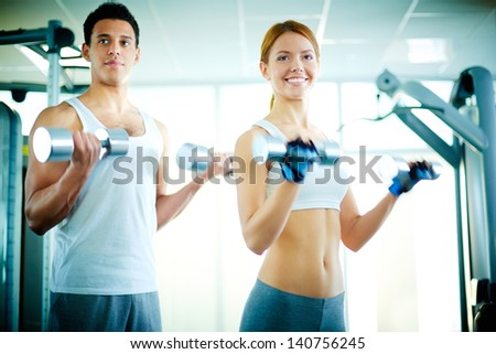 Portrait of pretty girl training in gym with young man near by - stock photo