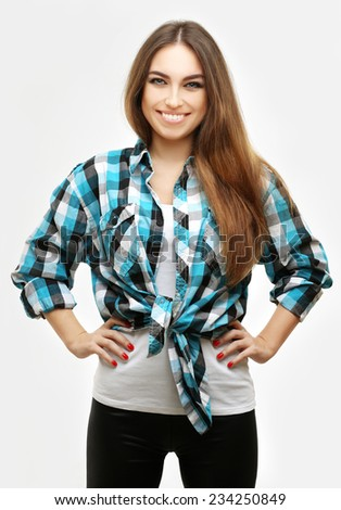 Portrait of pretty girl wearing blue shirt, laughing at camera. Gray background - stock photo