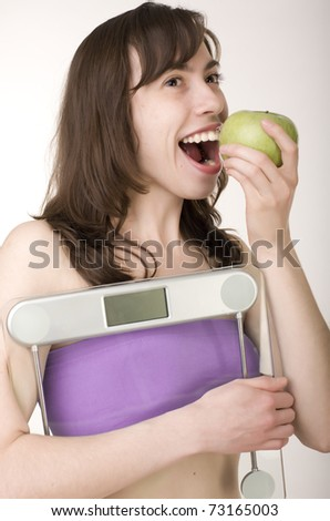 portrait of pretty girl wearing sports clothes holding scales and a measuring tape with green apple - stock photo