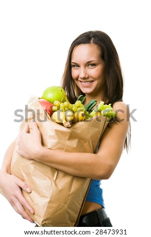 Portrait of pretty girl with big paper sack full of different fruits and vegetables looking at camera with smile
