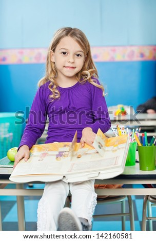 Portrait of pretty girl with book sitting on desk in classroom