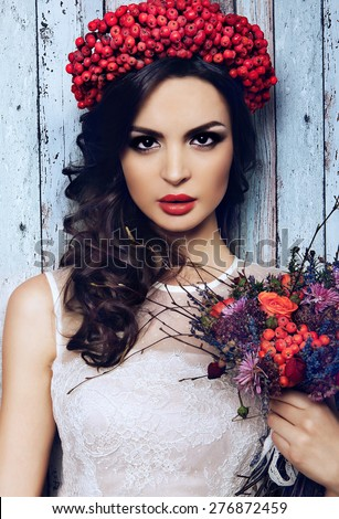 portrait of pretty girl with wreath of red berries and pigtail . Fashionable image , model with braid and red lips - stock photo