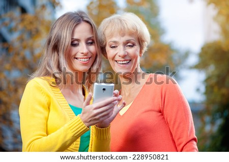 Portrait of pretty happy senior Mother with her smiling daughter using phone in the park - stock photo