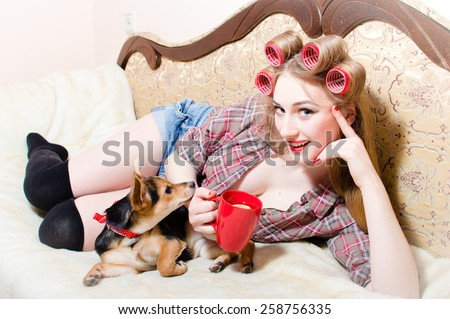 Portrait of pretty housewife at home relaxing lying in bed with cup and her dog - stock photo