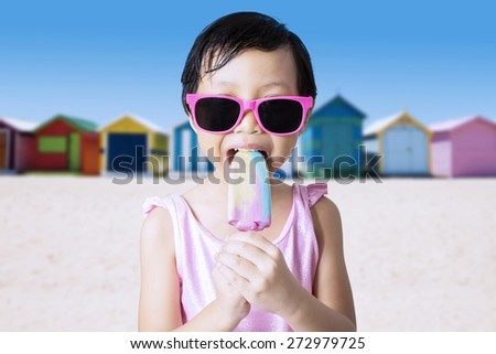Portrait of pretty kid enjoy cold ice cream on the seaside while wearing sunglasses and swimwear - stock photo
