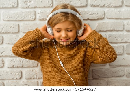Portrait of pretty little blonde girl listening to music and smilng while sitting against white brick wall - stock photo