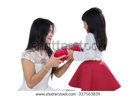 Portrait of pretty little girl giving a gift on her mother in the studio, isolated on white background - stock photo