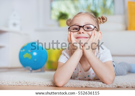 Portrait of pretty little girl lay on carpet at home with globe on background