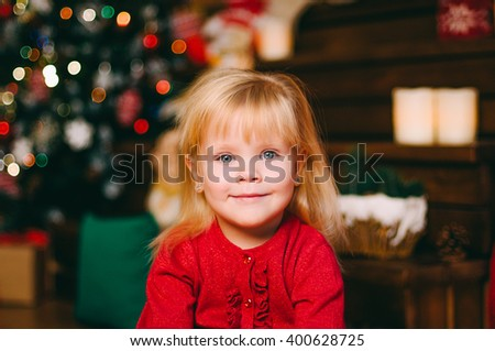 Portrait of pretty little girl looking into the camera over background with bokeh; Christmas studio decoration; shot in shallow depth of field  - stock photo