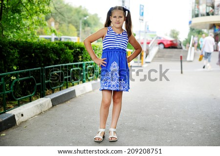 Portrait of pretty little girl walking at the city street