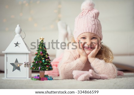 Portrait of pretty little girl with new years tree and flashlight at christmas time
