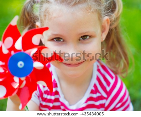Portrait of pretty little girl with red windmill - stock photo