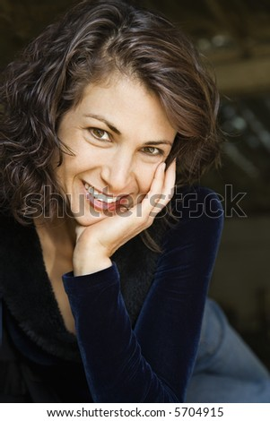 Portrait of pretty mid adult Caucasian woman smiling with head on hand making eye contact. - stock photo