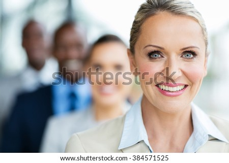portrait of pretty mid age businesswoman with colleagues standing in a row - stock photo