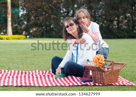 Portrait Of Pretty Mother And Daughter Having Picnic - stock photo