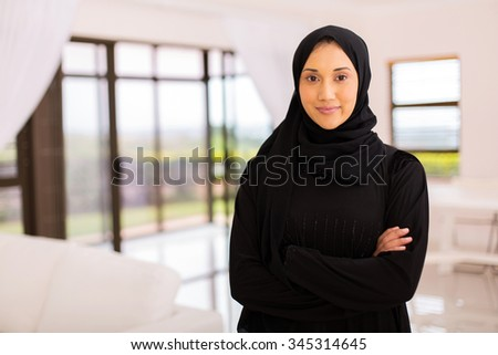 portrait of pretty muslim woman with arms crossed at home - stock photo