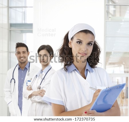 Portrait of pretty nurse at medical center, looking at camera.