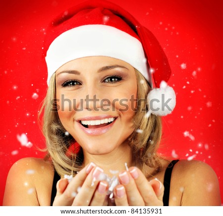 Portrait of pretty Santa girl laughing, isolated on red snowy winter holiday background - stock photo