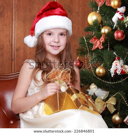 Portrait of pretty school girl decorating Christmas tree over bright festive background/Happy little girl with christmas present smiling - stock photo
