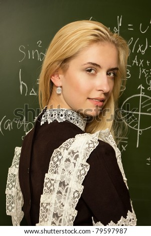 Portrait of pretty school girl in a classroom - stock photo