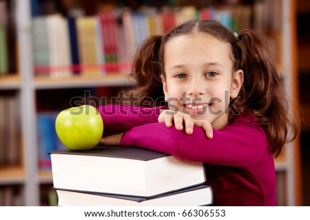 Portrait of pretty schoolgirl looking at camera with green apple on top of book heap near by - stock photo