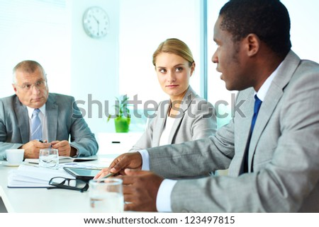 Portrait of pretty secretary and boss looking at employee at meeting - stock photo