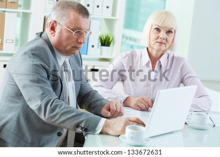 Portrait of pretty secretary looking at camera at workplace with her boss typing near by