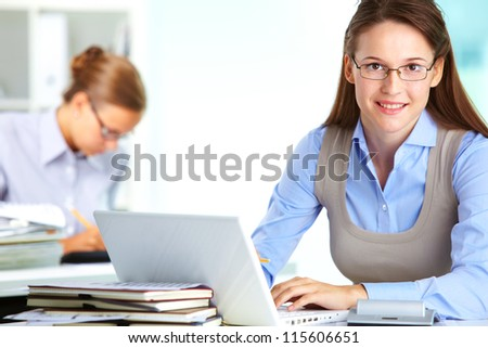 Portrait of pretty secretary looking at camera while typing in office